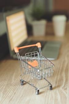 Conceito de compra online, carrinho de compras com laptop embaçado na mesa
