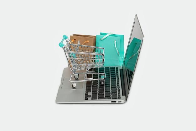 Conceito de compra online com computador laptop, sacola de compras e carrinho isolado no branco, copie o espaço
