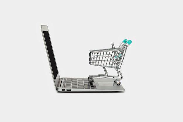 Conceito de compra online com computador portátil e carrinho de compras isolado no fundo branco, com espaço de cópia, close-up. comércio eletrônico