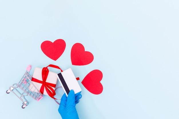 Conceito de compra seguro. uma mão em uma luva médica azul segura um cartão do banco acima de um carrinho de compras com uma caixa de presente