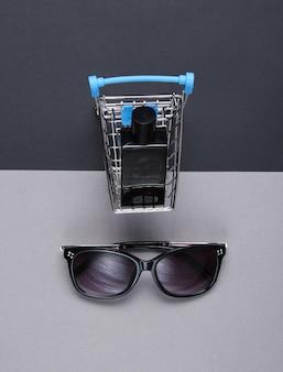 Conceito de comprador. frasco de perfume em mini carrinho de compras, óculos de sol na mesa de papel. vista do topo