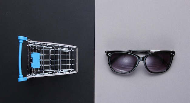 Conceito de comprador. mini carrinho de compras, óculos de sol na mesa de papel. vista do topo