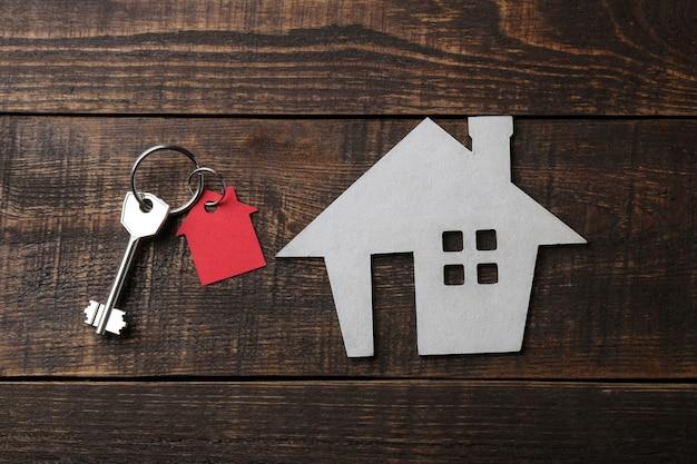 Conceito de comprar uma casa. casa decorativa com chaves e chaveiros em uma mesa de madeira azul. vista do topo