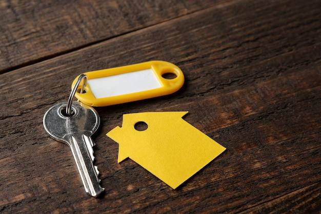 Conceito de comprar uma casa. chaves com um chaveiro e uma casa em um fundo de madeira marrom.