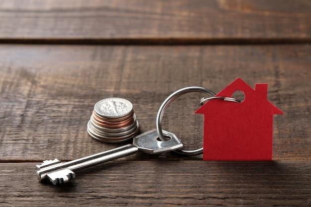 Conceito de comprar uma casa. chaves com uma casa de chaveiro e dinheiro em um fundo de madeira marrom. com espaço para inscrição