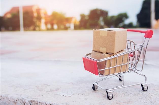 Conceito de compras: caixas ou caixas de papel no carrinho de compras no piso de concreto com espaço de cópia
