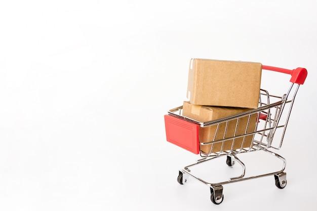 Conceito de compras: caixas ou caixas de papel no carrinho vermelho em branco com espaço de cópia