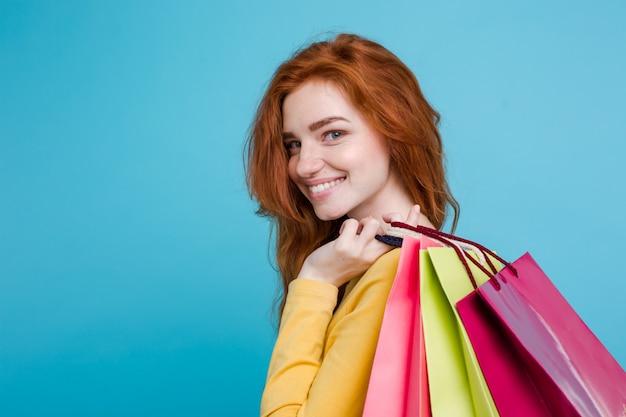 Conceito de compras - close up retrato jovem atraente atraente redhair menina sorridente olhando câmera com saco de compras. fundo pastel azul. copie o espaço.