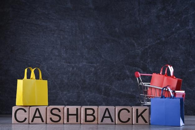 Conceito de compras. cubos de madeira com cashback de palavra com cesto de compras