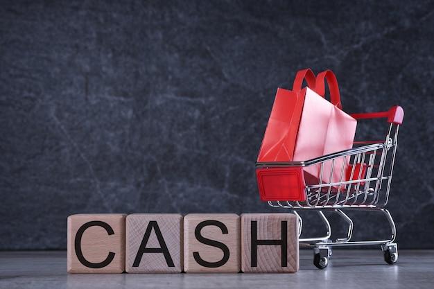 Conceito de compras. cubos de madeira com dinheiro de palavra barato na mesa escura com cesto de compras