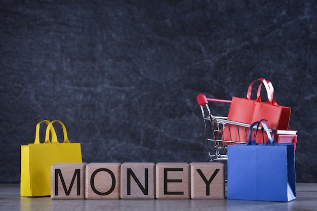 Conceito de compras. cubos de madeira com dinheiro de palavra com cesto de compras