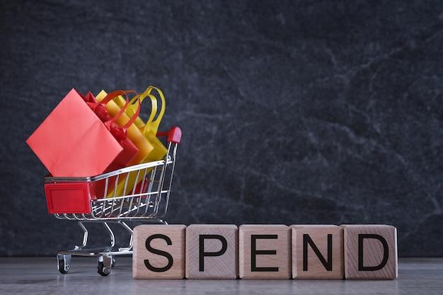 Conceito de compras. cubos de madeira com palavra gastam barato na mesa escura com cesto de compras