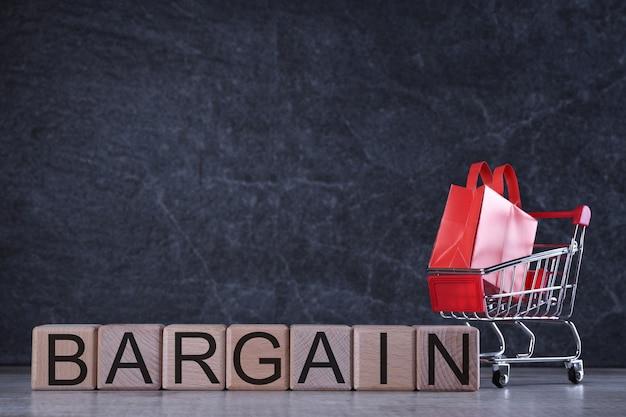 Conceito de compras. cubos de madeira com pechincha de palavra na mesa escura com cesto de compras
