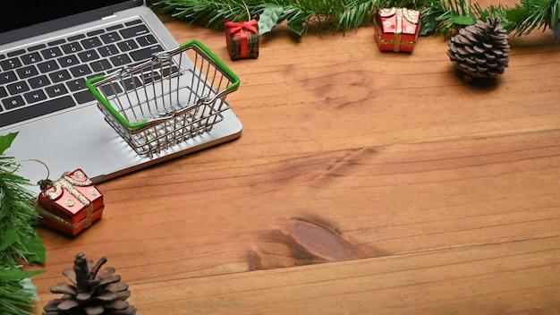 Conceito de compras de natal com decoração de natal com computador portátil e cesta.