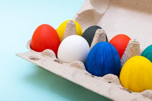 Conceito de compras de páscoa. close-up de ovos de páscoa pintados à mão em uma caixa de ovo de papelão. conceito de feliz páscoa.