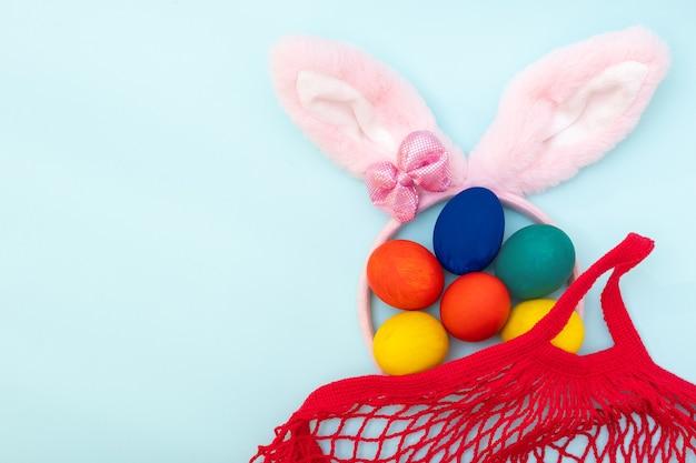 Conceito de compras de páscoa. ovos de páscoa de pintados à mão, orelhas de coelho rosa e uma sacola de compras vermelha sobre um fundo azul, cópia espaço, vista superior, plana leigos. conceito de feliz páscoa