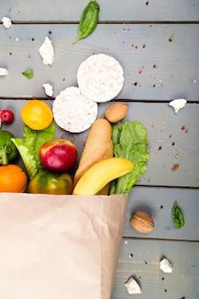 Conceito de compras de supermercado. alimento diferente no saco de papel em madeira. postura plana.