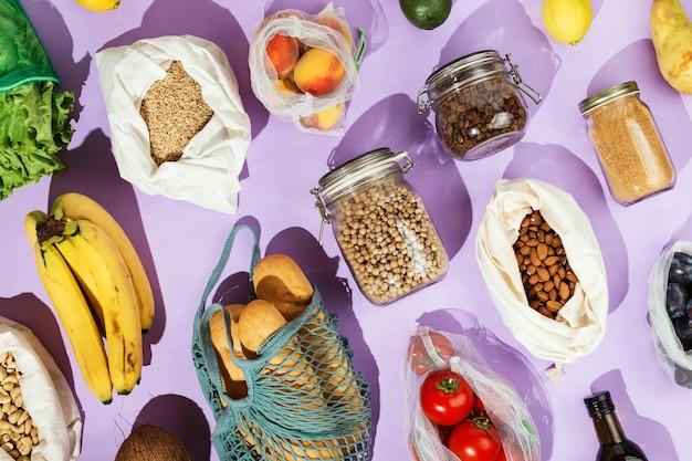 Conceito de compras de supermercado saudáveis com desperdício zero: leguminosas, frutas, verduras e legumes em redes de malha ou sacos de algodão e frascos de vidro