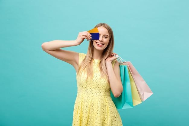 Conceito de compras e estilo de vida: linda garota com cartão de crédito e sacolas coloridas. isolado em um fundo azul.
