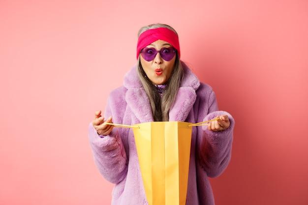 Conceito de compras e moda. mulher idosa asiática elegante de óculos escuros e casaco de pele sintética abre o saco de papel com presentes, parecendo surpresa com a câmera, fundo rosa