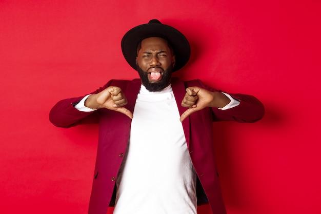 Conceito de compras e pessoas de natal. homem negro enojado mostrando a língua e os polegares para baixo, não gosto de algo ruim, julgando um produto horrível, fundo vermelho.