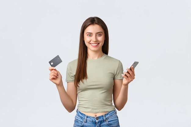 Conceito de compras, estilo de vida em casa e pessoas online. mulher atraente e elegante mostrando cartão de crédito e smartphone, sorrindo enquanto faz o pedido no aplicativo móvel, faz entrega em domicílio