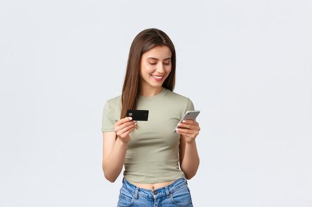 Conceito de compras, estilo de vida em casa e pessoas online. mulher atraente sorridente compra itens em loja da internet, usando cartão de crédito para pagar com telefone celular, fundo branco em pé