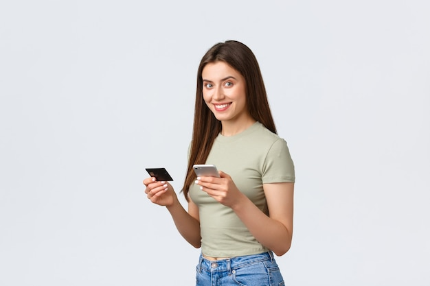 Conceito de compras, estilo de vida em casa e pessoas online. mulher atraente sorridente em roupas casuais, reserva de voo com smartphone, segurando o cartão de crédito e o celular para pagar a entrega, fazer o pedido.
