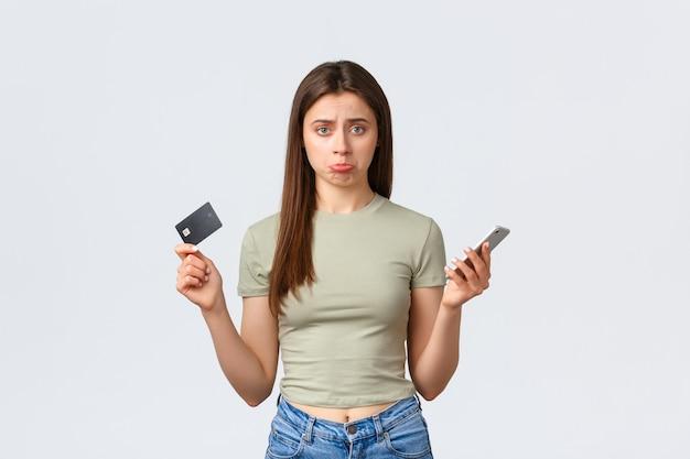 Conceito de compras, estilo de vida em casa e pessoas online. mulher de beicinho boba chateada mostrando cartão de crédito vazio e telefone celular, não posso fazer o pedido na loja da internet, fundo branco de pé.
