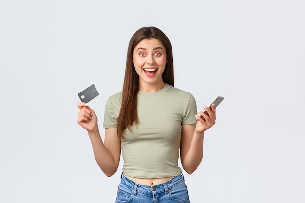 Conceito de compras, estilo de vida em casa e pessoas online. mulher feliz empolgada encontrou excelente loja de internet com descontos especiais, mostrando atônito e cartão de crédito.