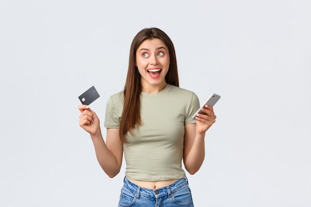 Conceito de compras, estilo de vida em casa e pessoas online. mulher morena feliz, alegre e sorridente, sonhando com um vestido novo, olhando para cima com alegria, segurando um cartão de crédito com o celular