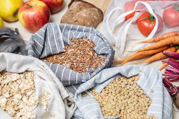 Conceito de compras éticas sem desperdício: alimentos veganos crus, incluindo frutas, legumes, arroz e cereais em embalagens bio