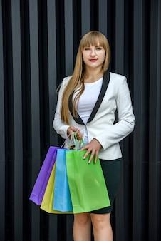 Conceito de compras. garota feliz com sacolas de compras, posando em fundo cinza do estúdio.