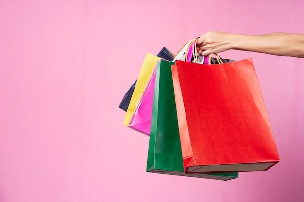Conceito de compras mão segurando sacolas coloridas