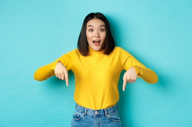 Conceito de compras. menina asiática atraente surpresa mostrando anúncio em fundo azul, apontando o dedo para baixo, olhando para a câmera e dizendo wow