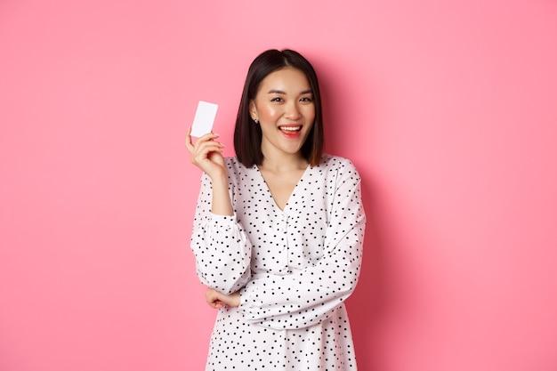 Conceito de compras. mulher asiática confiante e feliz, segurando o cartão de crédito e sorrindo satisfeito, em pé contra rosa.