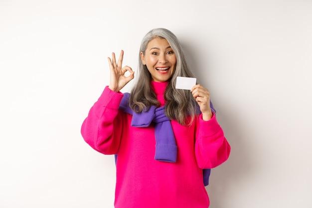 Conceito de compras. mulher asiática de meia-idade sorridente com cabelo grisalho, mostrando cartão de crédito de plástico e um sinal de ok, recomendando promoção de banco, fundo branco