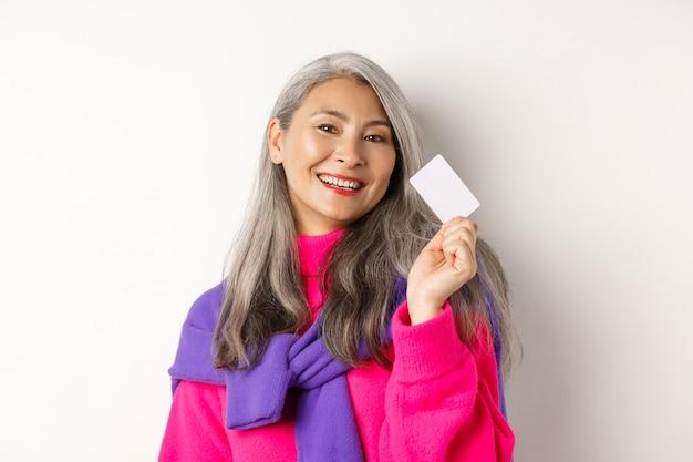 Conceito de compras. mulher asiática sênior elegante sorrindo e mostrando o cartão de crédito de plástico, pagando sem contato, em pé sobre um fundo branco.