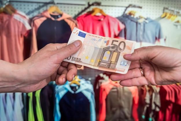 Conceito de compras. o cliente paga euros na loja. notas de euro