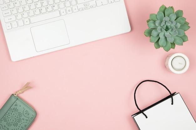 Conceito de compras on-line. as mãos das mulheres com telefone e laptop na superfície rosa. vista superior, copie o espaço.