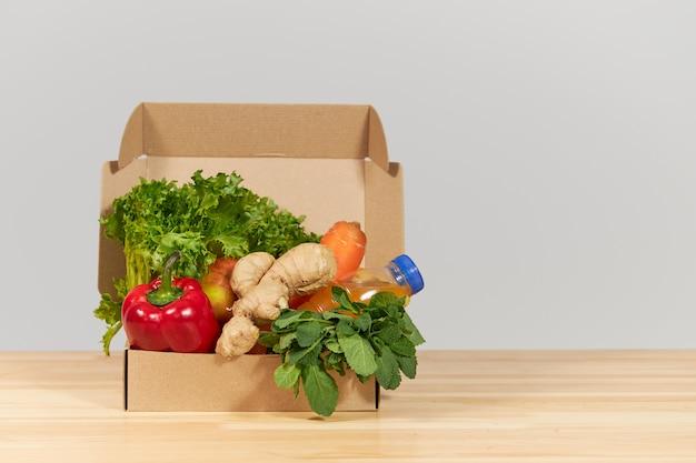Conceito de compras on-line. caixa de supermercado com frutas e legumes frescos. entrega em domicílio de alimentos durante o coronavírus em quarentena