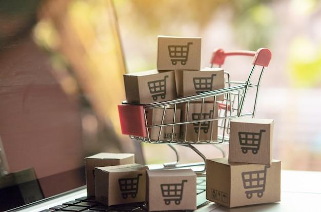 Conceito de compras on-line - caixas de papel ou pacote com um logotipo de carrinho de compras em um carrinho