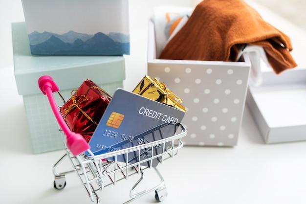Conceito de compras on-line. carrinho de compras, caixas de encomendas, cartão de crédito, sobre a mesa em casa. copie o espaço, close-up