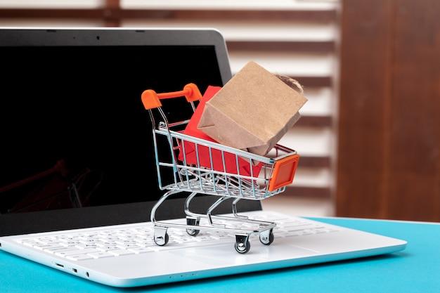 Conceito de compras on-line. carrinho de compras, laptop na mesa