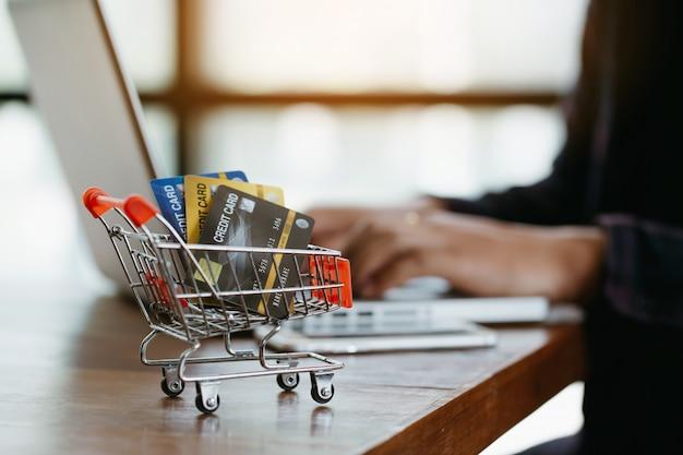 Conceito de compras on-line. cartão de crédito no mini carrinho de compras.
