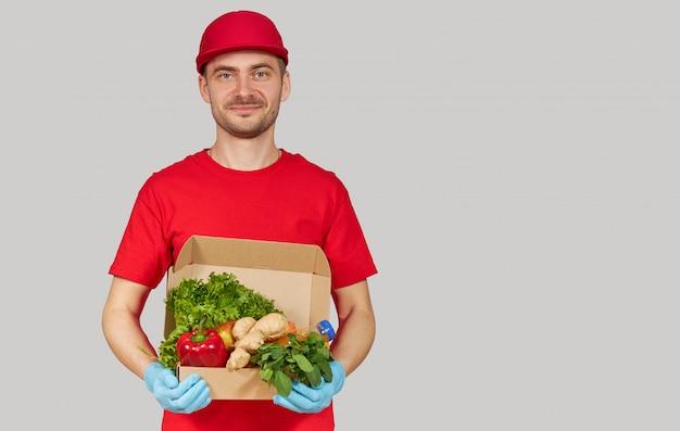 Conceito de compras on-line. correio masculino em uniforme vermelho e luvas com uma caixa de supermercado com frutas e legumes frescos. comida para entrega em domicílio