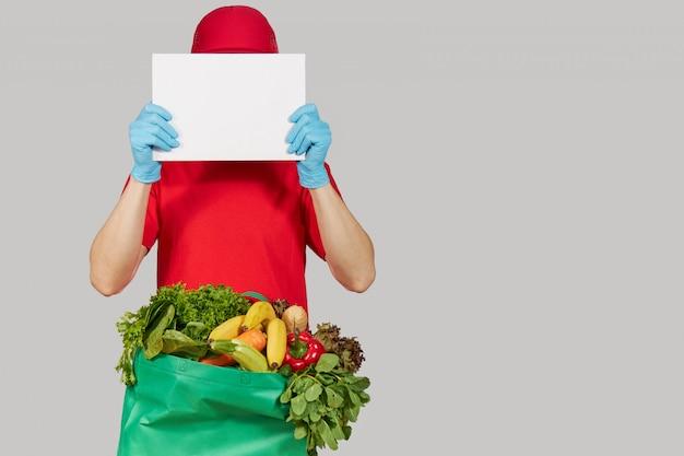 Conceito de compras on-line. correio masculino em uniforme vermelho, máscara protetora e luvas com frutas e legumes frescos de uma caixa de supermercado mantém uma bandeira branca para texto. comida para entrega em domicílio durante a quarentena