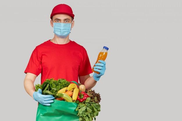 Conceito de compras on-line. correio masculino em uniforme vermelho, máscara protetora e luvas com uma caixa de supermercado com frutas e legumes frescos. comida para entrega em domicílio durante a quarentena