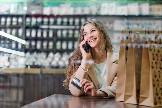 Conceito de compras on-line. mulher com sacos de papel no café, segurando o cartão de crédito nas mãos e falando no telefone.