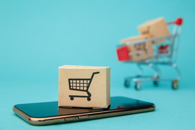 Conceito de compras online. caixas e sacola de compras acima do smartphone em azul.